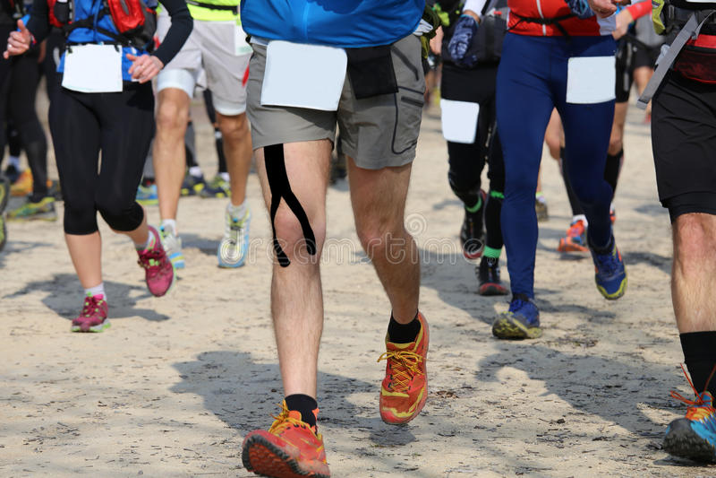 Biegacze biegają na drodze podczas gdy jadący w rasie obraz stock