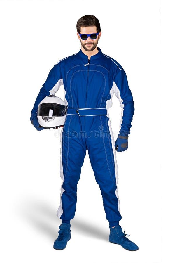 Biegowy kierowca w błękitnych białych motorsport kombinezonu butów rękawiczkach i zbawczy przekładnia trzaska hełm pod jego ręką  zdjęcie stock
