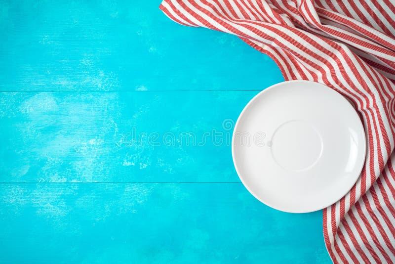Biel czerwień i paskowaliśmy tablecloth na błękitnym drewnianym tle obraz stock
