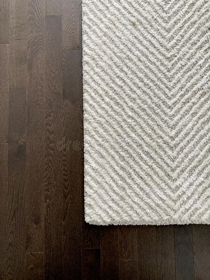Biel i Popielaty szewronu dywanik na ciemnej harwood podłogi teksturze Mistrzowska sypialnia w nowożytnym luksusu domu zdjęcia stock