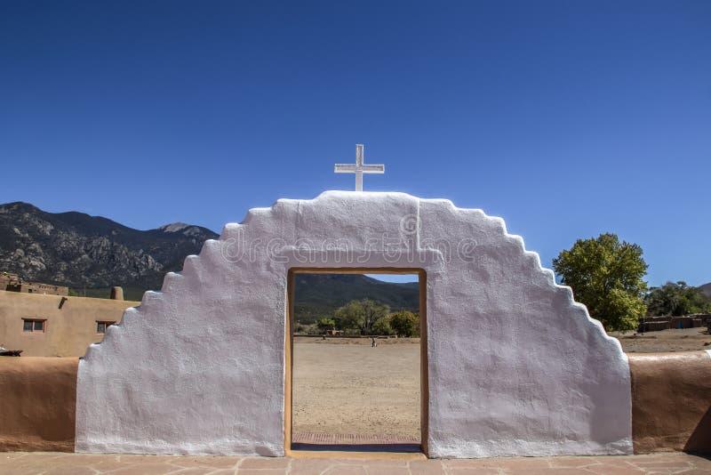 Biel malował borowinową adobe bramę z krzyżem na odgórny patrzeć z misji podwórza na górach, drzewa i osada mieszkaniec zdjęcie royalty free