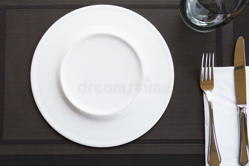 Biel puści talerze z rozwidleniem i nożem wiązali z faborkiem obrazy stock