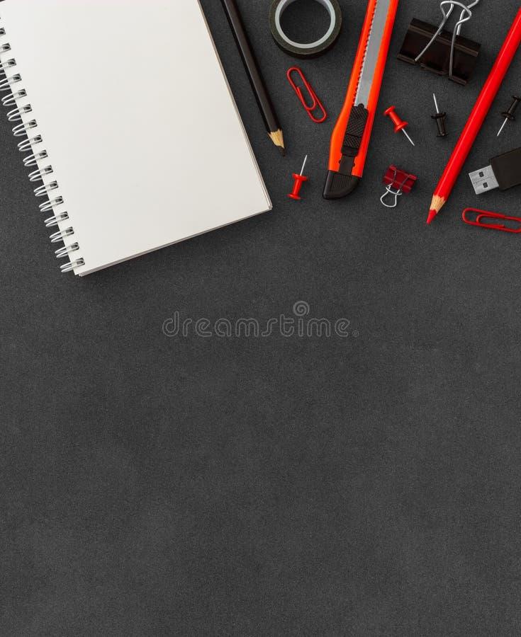 Biel spirali papieru notatnik z krajacza no?em, papierowe k?py, papierowe klamerki, pchni?cie szpilki, barwioni o??wki na ciemnym obraz royalty free