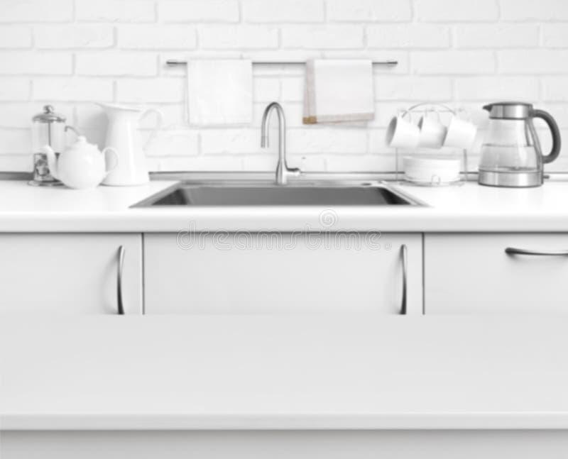 Biel uwarstwiał stół na zamazanym nieociosanym kuchennego zlew wnętrza tle zdjęcia stock