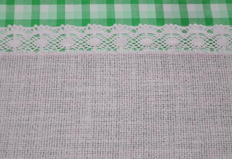 Bieliźnianego płótna tkanina z koronkowym koronkowym faborkiem i granica zielony tartanu wzór obraz royalty free