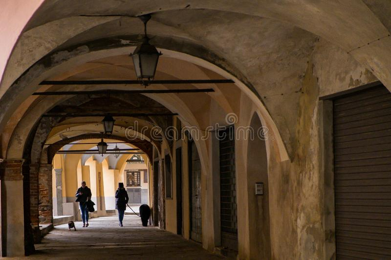 Biella, Piedmont - Italy. BIELLA - MARCH 02, 2015: walking under the portici in the higher part of town, the Piazzo with the medieval streets stock image