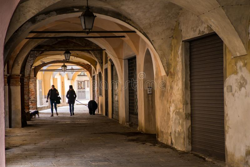 Biella, Piedmont - Italy. BIELLA - MARCH 02, 2015: walking under the portici in the higher part of town, the Piazzo with the medieval streets royalty free stock image
