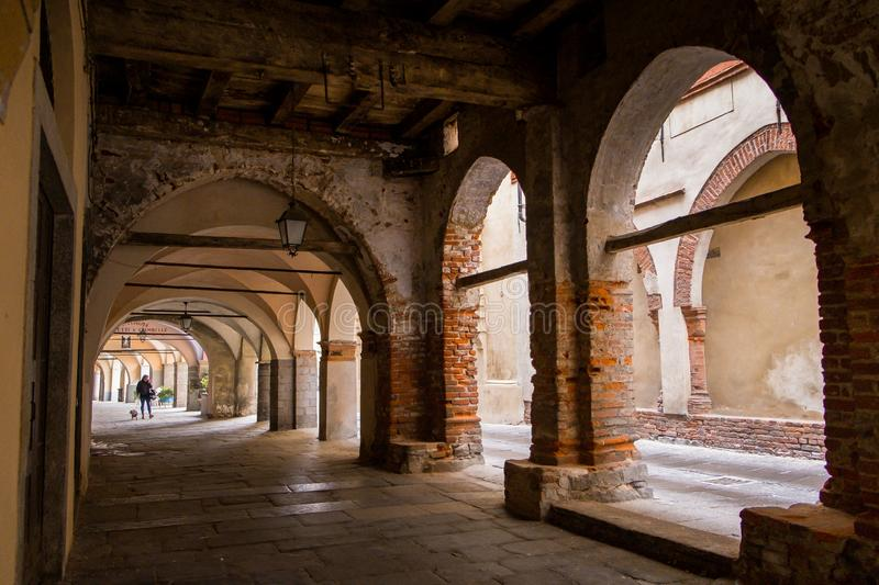 Biella, Piedmont - Italy. BIELLA - MARCH 02, 2015: walking under the portici in the higher part of town, the Piazzo with the medieval streets royalty free stock images