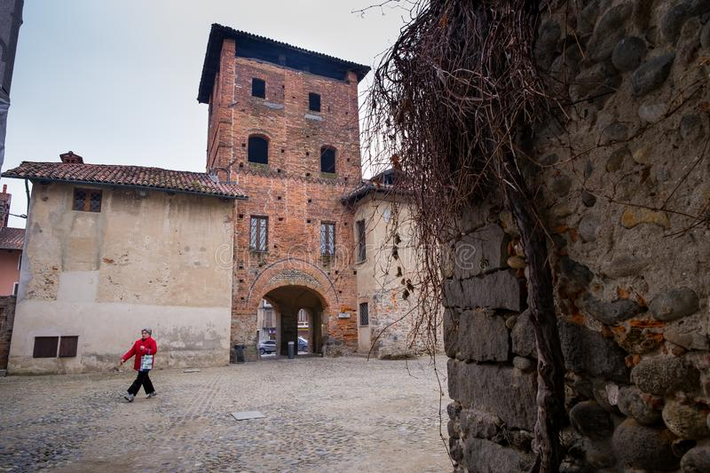 Biella, Piedmont - Italy. CANDELO, BIELLA - MARCH 02, 2015: Unknown man walking in the ancient village in Ricetto of Candelo, Biella province, Piedmont, Italy royalty free stock images