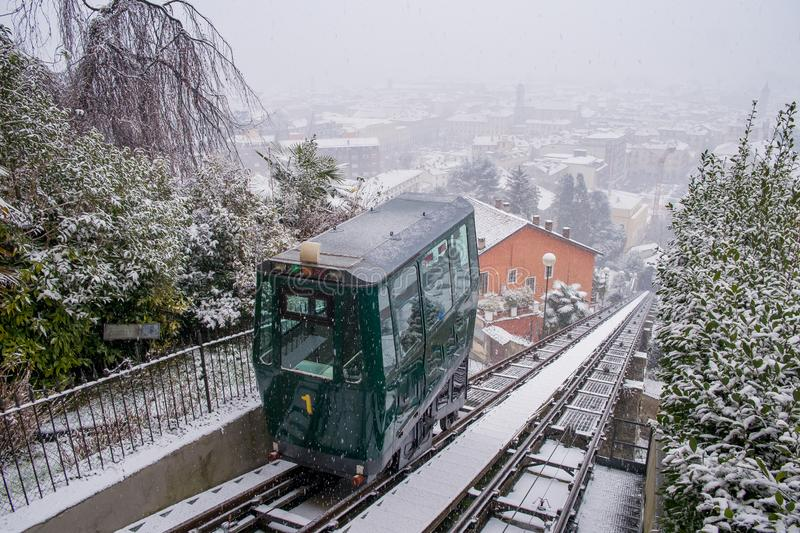 Biella, Piedmont - Italy. Biella, looking down to the town from the funicular station in the higher part of town during the snowfall, the Piazzo stock photography