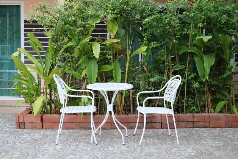 Bielu żelaza stół i krzesła, siedzący kąt, piękny zielony drzewny tło obrazy royalty free