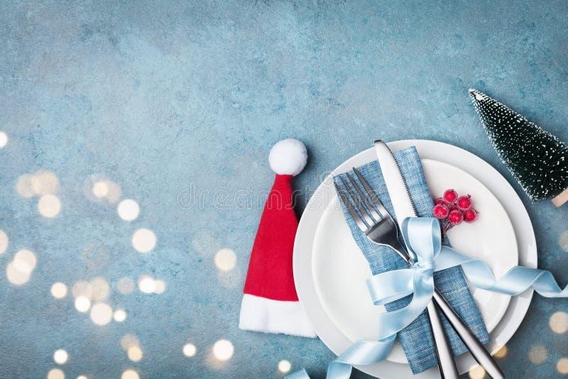 Bielu cutlery i talerz dekorowaliśmy Santa kapelusz i małego jedlinowego drzewa Boże Narodzenia zgłaszają położenie od above obraz royalty free
