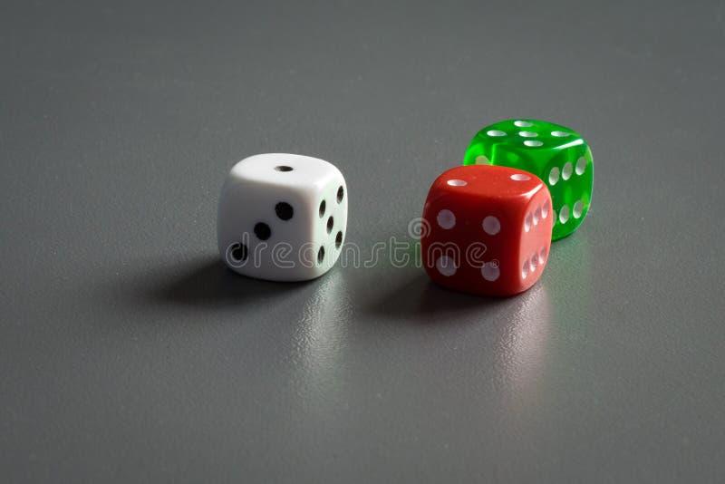 Bielu, czerwieni i zieleni kostki do gry na zmroku, siwieją tło obraz royalty free