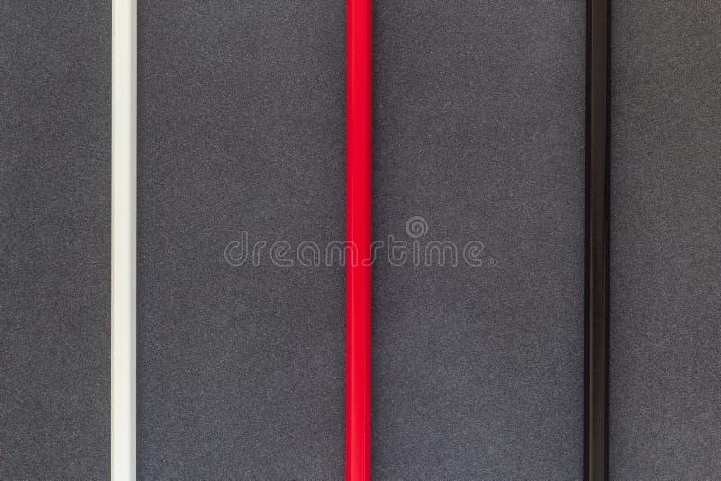 Bielu, czerwonych i czarnych barwioni pecnils, wykładają na ciemnego backgroung odgórnym widoku obraz stock