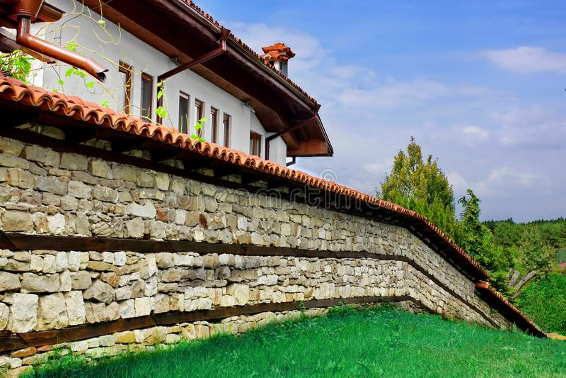 Bielu dom, kamienia ogrodzenie z Dachową płytką i gazon, obrazy stock