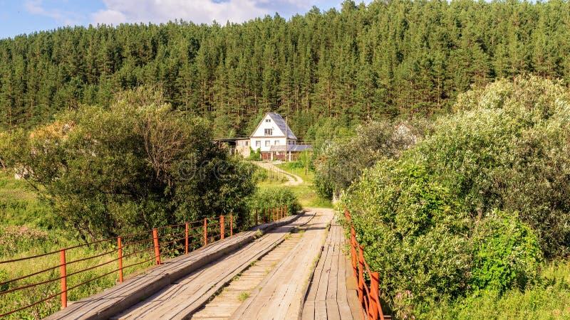 Bielu dom w sosnowym lesie z drewnianym mostem fotografia royalty free