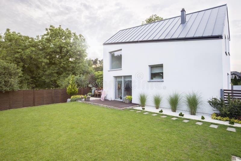 Bielu dom z przestronnym ogródem i zielona trawa podczas wiosny Istna fotografia obraz stock