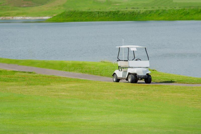 Bielu golfowy samochód w zielonym polu golfowym fotografia stock