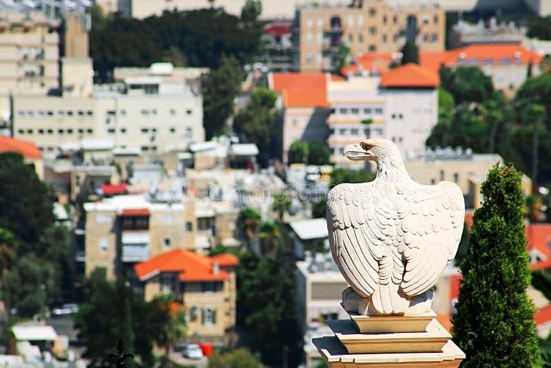Bielu kamienny orzeł chroni bramę Bahai ogródy i przegapia pejzaż miejskiego Haifa zdjęcia stock