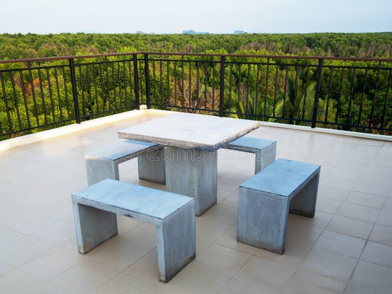 Bielu marmuru ławki stołu biurko i marmuru krzesło na dachu wierzchołku z zielonym naturalnym namorzynowym widokiem zdjęcia stock