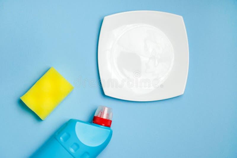Bielu pusty szklany talerz, pusta czysta butelka i piany gąbka dla myć naczynia, obrazy stock