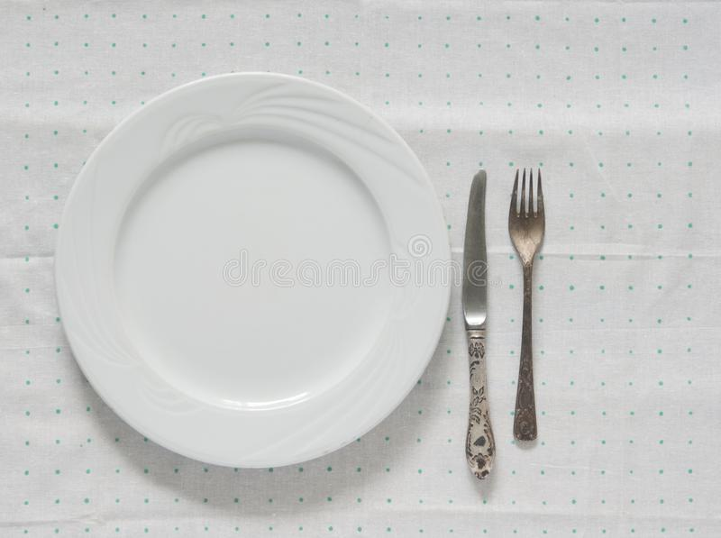 Bielu pusty talerz z rozwidleniem i nóż na polki kropki tablecloth zdjęcia stock
