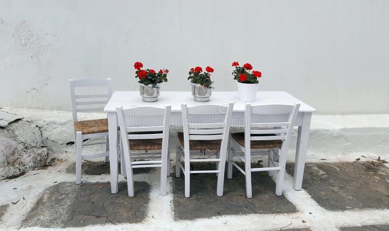 Bielu stół z pięknymi floewers i krzesłami w ulicznej restauracji w Mykonos wyspie zdjęcie stock