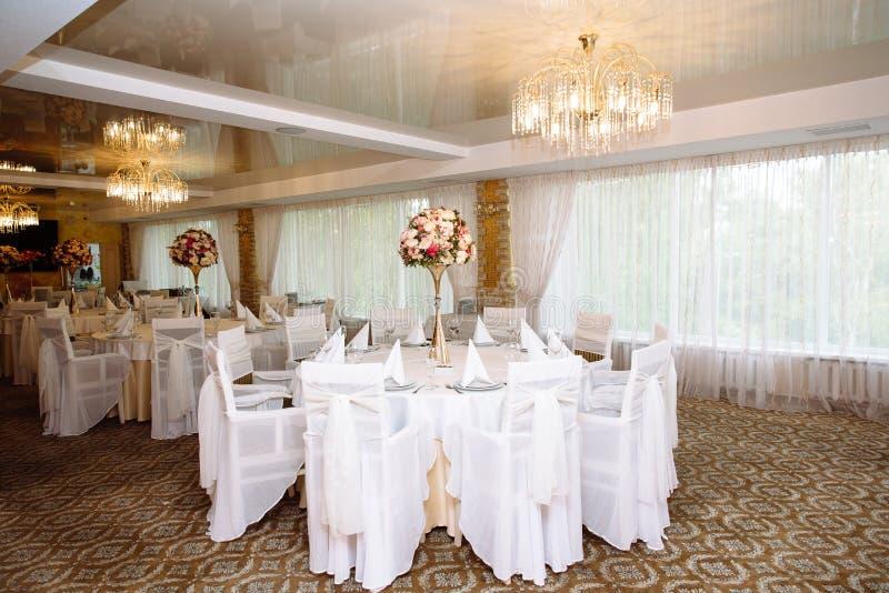 Bielu stołowy położenie przy weselem, czyści stoły z kwiatami i żadny jedzeniem w restauraci Pojęcie ślub lub obraz royalty free
