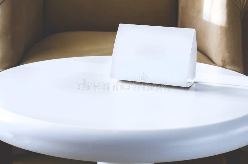 Bielu szyldowy karton z kopii przestrzenią na białym round stole Hotelowy wn?trze fotografia royalty free