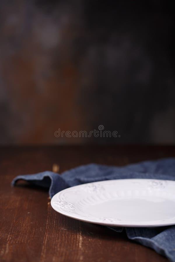 Bielu talerz na drewnianym tle, błękitny płótno na stole obrazy royalty free
