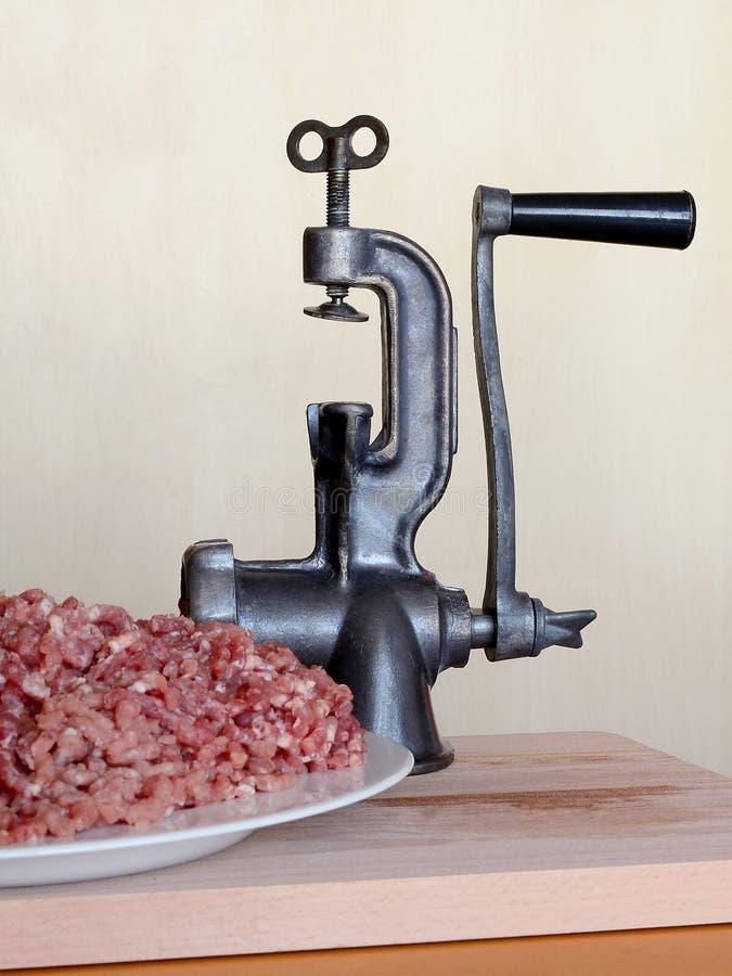 Bielu talerz z i rocznika ręczny maszynka do mięsa obracający do góry nogami na drewnianej tnącej desce na beżowym tle mince, fro zdjęcie royalty free