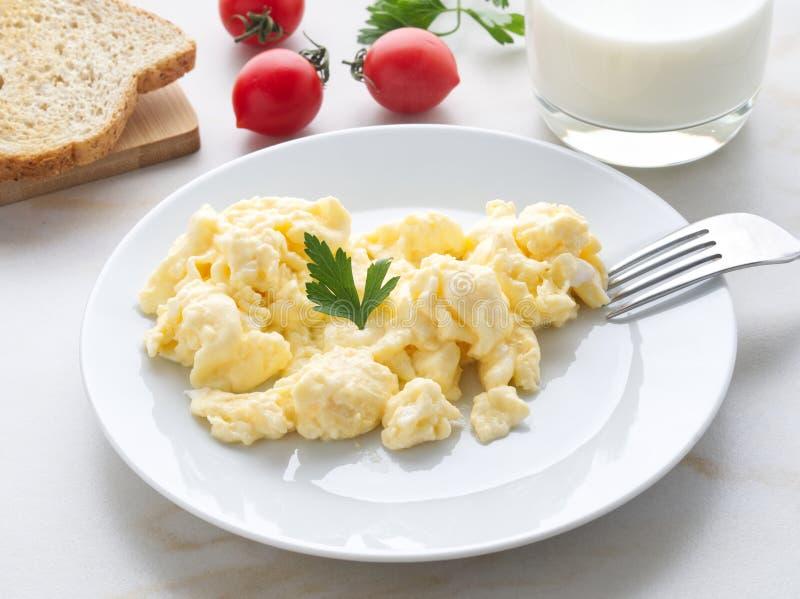 Bielu talerz z smażącymi rozdrapanymi jajkami na światła białego tle z pomidorami Omelette, boczny widok obraz stock