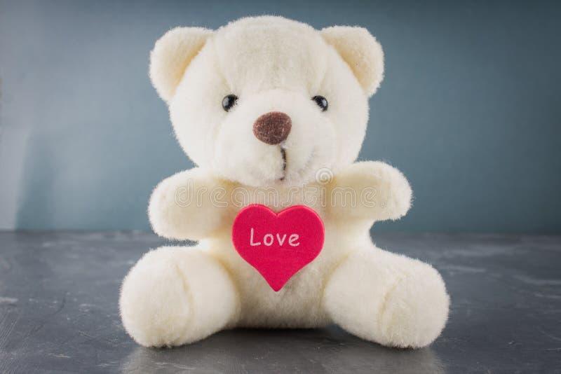 Bielu zabawkarski miś z sercem na szarym tle Symbol fotografia stock