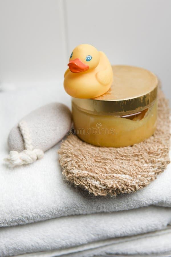 Bien-être, canard en caoutchouc, pierre ponce et gant sur les serviettes blanches photographie stock libre de droits