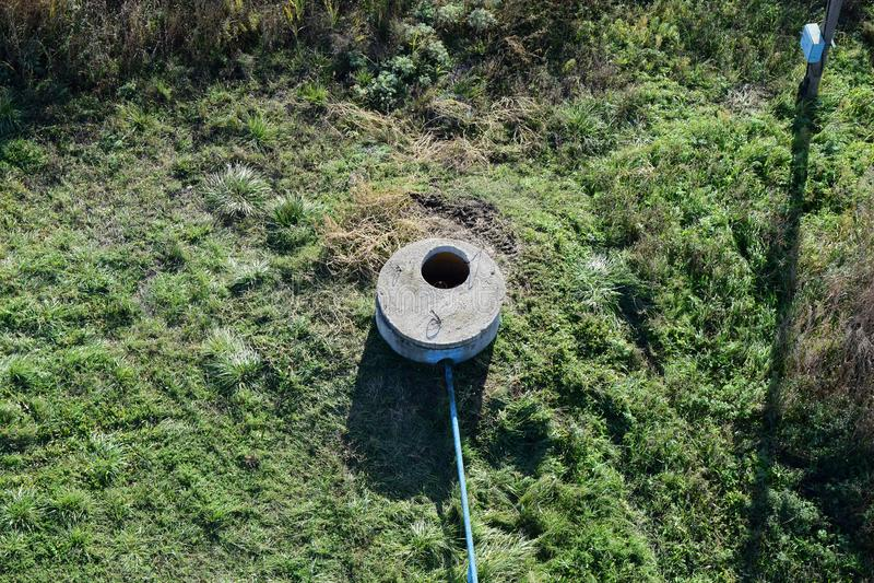 Bien d'un puits artésien avec une pompe submersible Couvert de puits concret photos stock