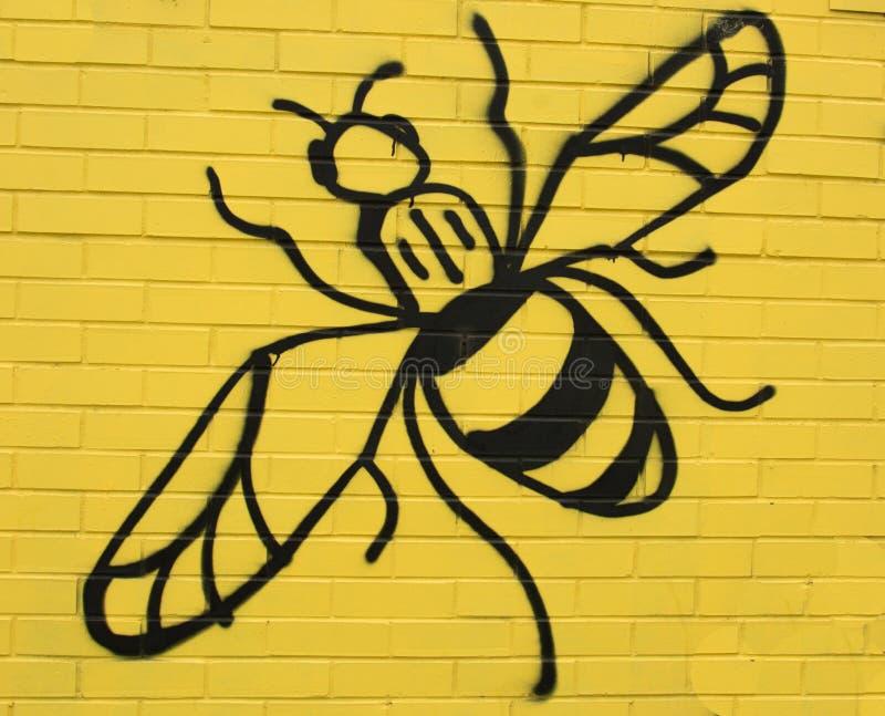 Bienen-Zahl auf gelber Wand stockfotografie