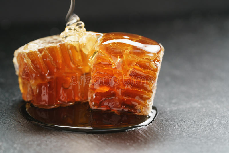 Bienenhonig gießt über Bienenwabe auf Schieferbrett lizenzfreie stockbilder