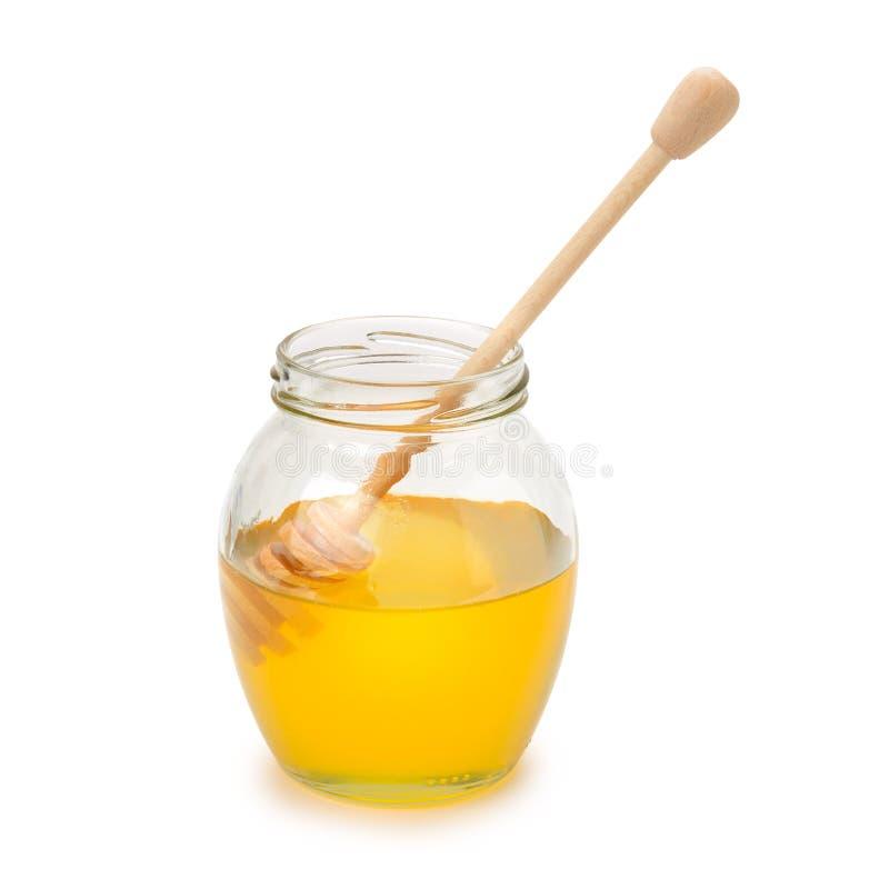 Bienenhonig im Glasgefäß und in hölzernem Löffel lokalisiert auf Weiß lizenzfreie stockfotos