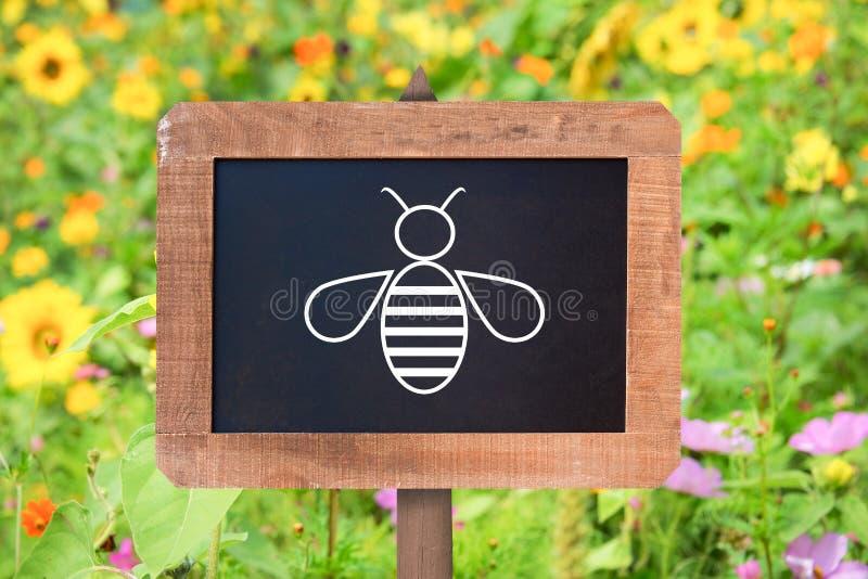 Bienenikone auf einem Holzschild, Hintergrund der wilden Blumen Bienenerhaltungs-Zonenkonzept lizenzfreie stockfotos