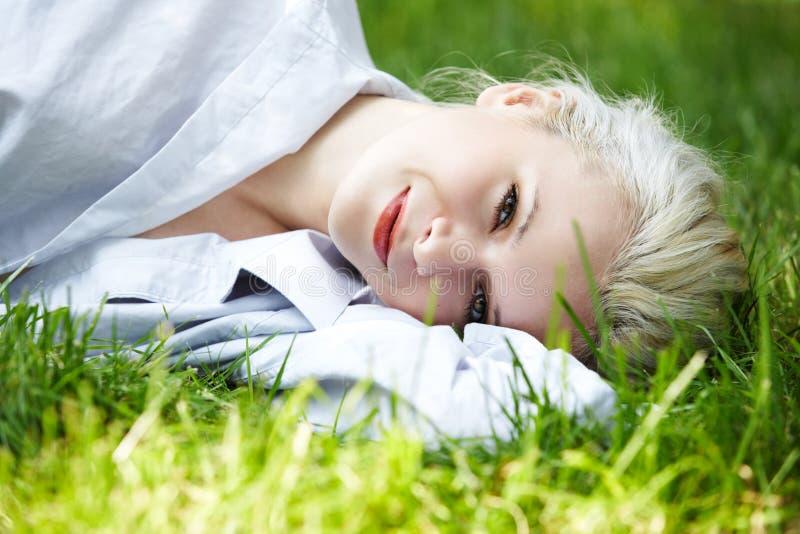Bienestar. La mujer sonriente feliz tiene resto en hierba foto de archivo