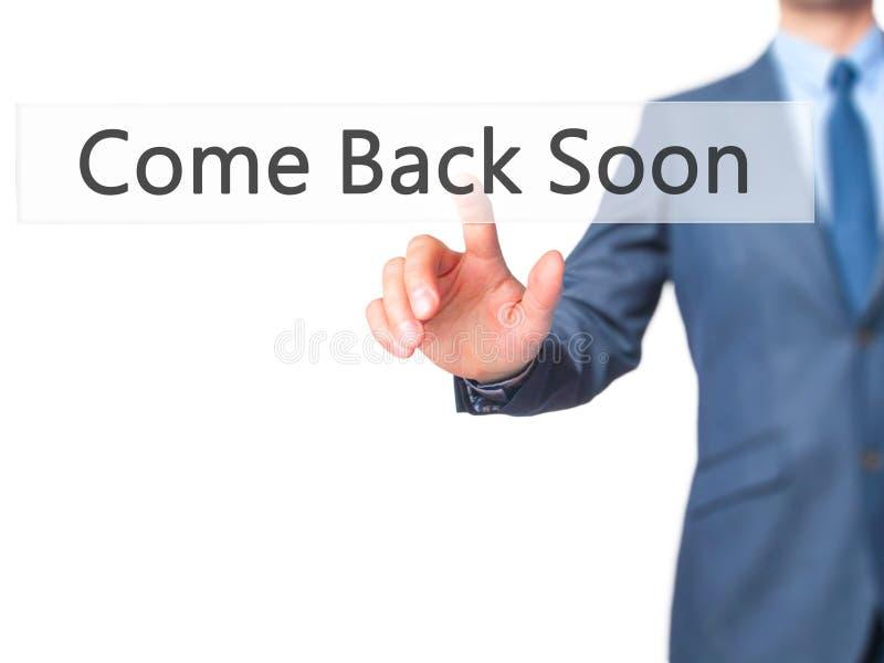 Bientôt revenu - bouton de pressing de main d'homme d'affaires sur l'éboulis de contact images stock