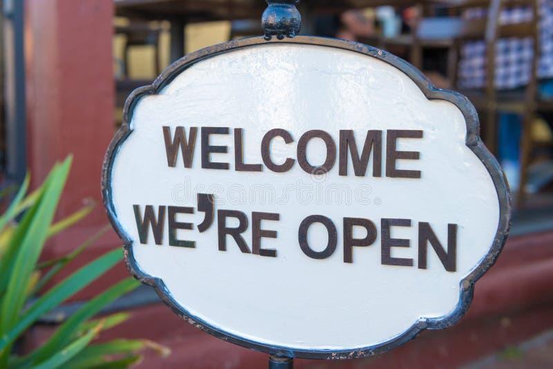Bienvenu nous sommes signe ouvert à l'entrée de restaurant photos stock
