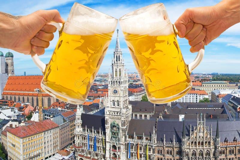 Bier übergibt Beifall mit München Marienplatz im Hintergrund stockfotografie