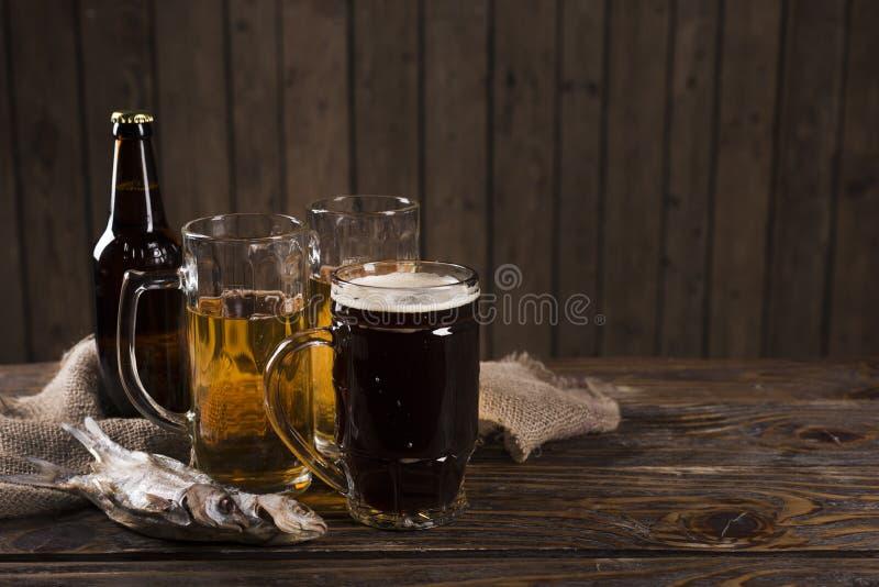 Bier auf dem alten Holztisch rustikal lizenzfreie stockbilder