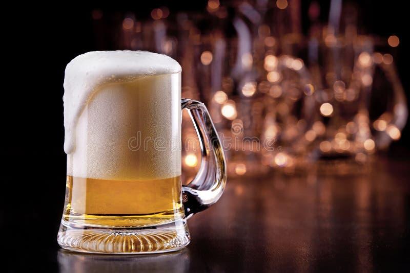 Bier auf hölzerner Tabelle stockfotografie