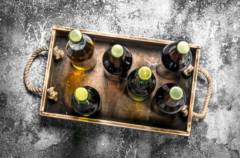 Bier in den Flaschen auf einem hölzernen Behälter stockfotografie