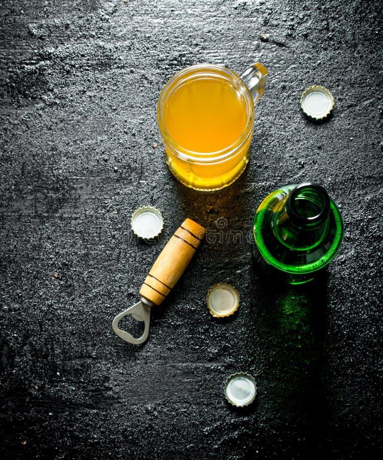 Bier in einem Glas und in einer offenen Glasflasche mit ?ffner stockfotos