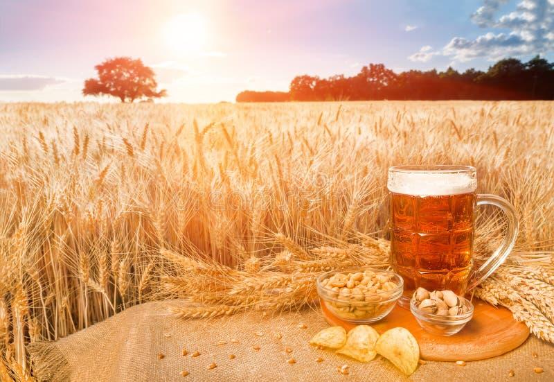 Bier en snacks op het achtergrondtarwegebied stock afbeelding