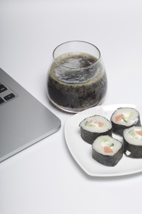Bier en sushi Tribune dichtbij laptop Rust met voedsel en gadgets stock afbeeldingen