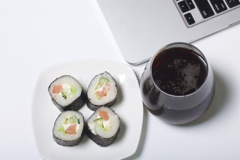 Bier en sushi Tribune dichtbij laptop Rust met voedsel en gadgets stock afbeelding